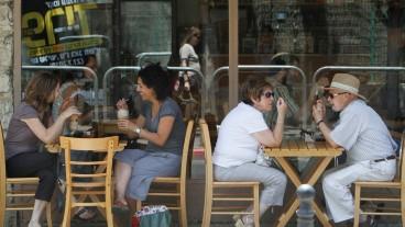 Residentes del barrio disfrutan de un día soleado en un café callejero. Foto deMiriam Alster/Flash90.