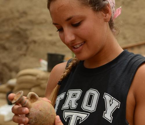 Una estudiante examina una vasija de los siglos noveno a décimo, antes de esta era, que fue hallada cementerio. Foto de Melissa Aja/Expedición Leon Levy.