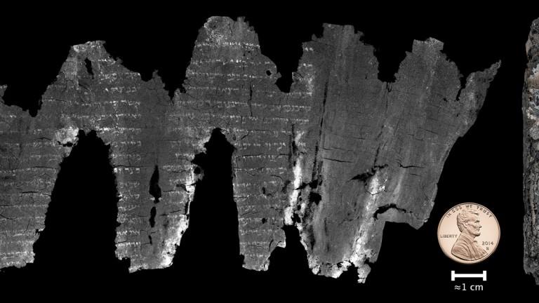 El rollo, encontrado en Ein Gedi, fue desenrollado digitalmente debido a su frágil condición. La moneda a la derecha de una idea de su tamaño. Foto cortesía de Brent Seales.