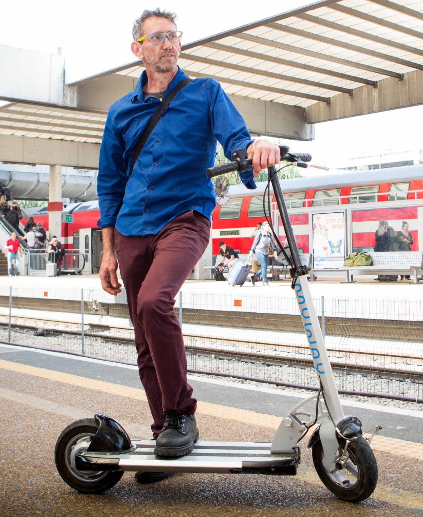 El diseñador de Inokim, Nimrod Sapir, con una de sus scooters en una estación de tren en Israel. Foto de Shlomi Yosef.